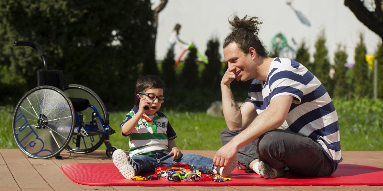 Lille dreng sidder på terasse med sin mandlige hjælper
